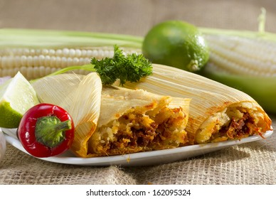 Mexican tamale wrapped in corn husk served on plate.
