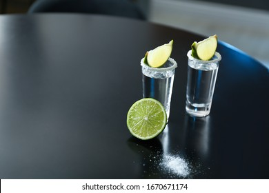 Mexican Tequila with salt and lime slices on black table at bar. Space for text