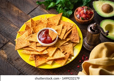 Mexican tortilla chips Nacho with tomato sauce and salsa on yellow plate, wooden background. Tex mex food