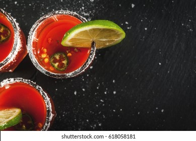 Mexican traditional alcohol drink. Sangrita, with tequila, tomato juice, hot spices, chili and lime.Analogous bloody mary. On black slate table, copy space top view