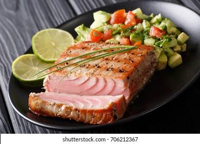 Mexican tuna steak with avocado cucumber salsa closeup on a plate. horizontal