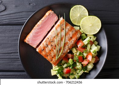 Mexican tuna steak with avocado cucumber salsa closeup on a plate. Top view from above horizontal