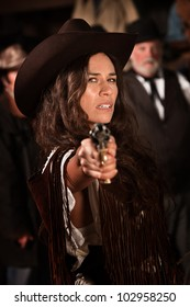 Mexican woman in old west style clothes points a revolver