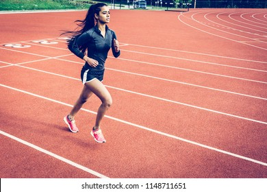 Mexican woman sprinting on a track. Long black hair in a pony tail, long sleeve top, shorts and pink runners.