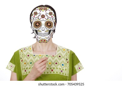 Mexican woman in traditional clothing wearing skull mask Catrina celebrating Day of the Dead.