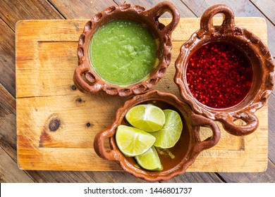 Mexican-style mud pots, contains green sauce, chile de árbol sauce and lemons, are a classic accompaniment to Mexican food, to put in all kind of meals. It has a spicy flavor.