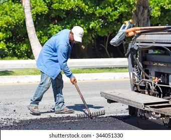 Mexico, Cancun - 10 October 2015: Worker making asphalt with rake at road construction