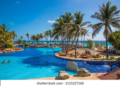 Mexico, Cancun - February 15, 2018: Grand Pyramid hotel swimming pool with palms and sunbeams. People chilling out by the water.