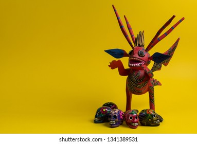 Mexico City, Mexico; 03/15/2019: Photo of the figure of a mexican alebrije with some handmade skulls on a yellow solid background with Copy space for Editor's text.