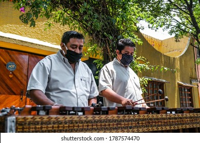 Mexico City, Mexico, 07/04/2020: Mexican musicians playing Marimba in the street, wearing face masks as protection due coronavirus. Playing typical music from Veracruz.