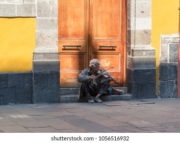 Mexico, Mexico City- 16 January  2017: old beggar violinist plays the seated violin, frontal photo