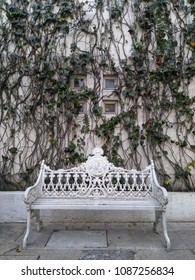 MEXICO CITY, MEXICO, 2018-01-10: white metal bench with sign Republica Mexicana next to the wall covered with ivy