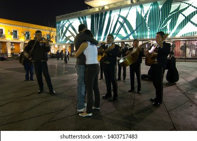 Mexico City, Mexico - 2019: Mariachis perform for a young couple at Garibaldi Square (Plaza Garibaldi) on a Sunday night.