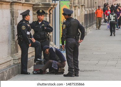 MEXICO CITY, MEXICO, 21.1.2012: A group of police officers are getting their shoes cleaned by a street cleaner on a busy street
