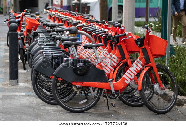 Mexico City - April 10 2020:  Parked red Jump bikes provided by Uber are available to hire. Communal city electric bicycles project is effort to make city transportation more ecological and healthy.