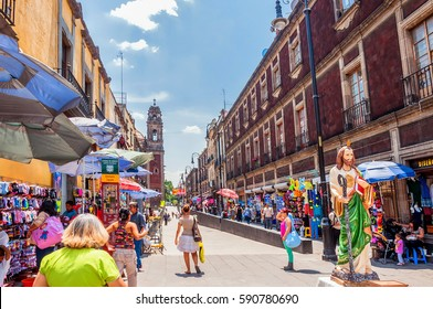 MEXICO CITY, MEXICO - APRIL 29, 2014: locals and tourists in Zocalo downtown streets in Mexico City, Mexico. The city is located at an altitude of 2,240 meters