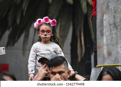Mexico City, CDMX/Mexico--October 26, 2019. A young girl watches the Mega Catrina Procession celebrating Day of the Dead, which began at the Angel of Independence Statue.