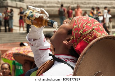 Mexico city / Mexico - Circa 2014: A charro drinking tequila from the bottle in the 2014 Gay Parade at Mexico city. This parade have been every year a big party to celebrate diversity and love.