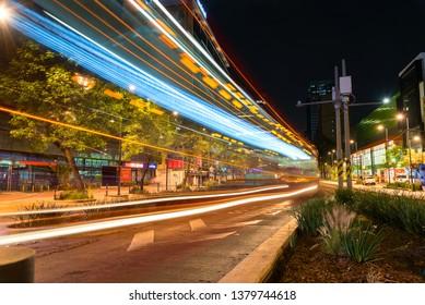 MEXICO CITY, MEXICO / CIRCA APRIL 2019: Metrobus trail lights at Insurgentes and Distribuidor Mixcoac, night scene
