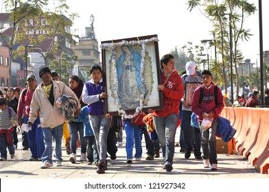 MEXICO CITY - DEC 12: Faithful Catholics march towards the basilica of Our Lady of Guadalupe carrying her image in celebration of the Virgin on December 12, 2012 in Mexico City