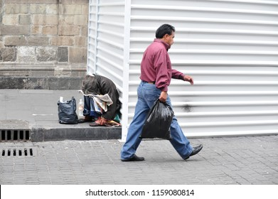 MEXICO CITY - FEB 24 2010: Mexican man passing by homeless Mexican woman in Mexico City, Mexico. 44 percent of the Mexican population, over 49 million, lives below the poverty line.