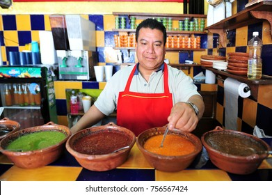 MEXICO CITY - FEB 27 2010: Mexican chef prepares hot sauces in Mexican restaurant wait in Mexico City, Mexico.Authentic Mexican food is low in fat, while being high in minerals and vitamins.