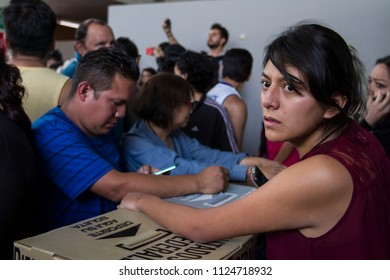 Mexico City. July 1, 2018. A citizen in charge of the special polling place takes care of the votes while annoyed persons complain because the electoral ballots finished before everyone could vote.