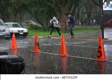 MEXICO, MEXICO CITY - July 10th 2017; man and woman rushing to cross the street under heavy rain and flooded road