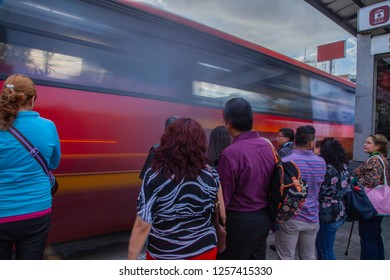 Mexico City - July 12, 2018: pedestrians waiting for the green light to be able to cross the insurgent avenue and in the background a metrobus car passing in front of them