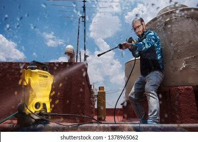 MEXICO CITY, MEXICO - JULY 17, 2018: Cleaning the rooftop with a waterjet using a Karcher machine.