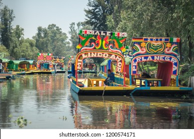 "Mexico City, Mexico - July 29, 2018: So called ""trajineras"" ,that are colorful boats pushed by sticks, wait on a canal to pick up a group of people in Xochimilco."