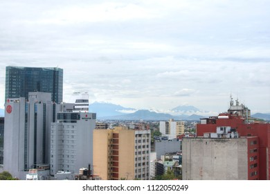 MEXICO CITY, MEXICO - JUNE 19, 2018: Many tall buildings in Mexico City have a clear view of the famous Popocatepetl y Iztaccihuatl volcanoes to the southeast of the city.