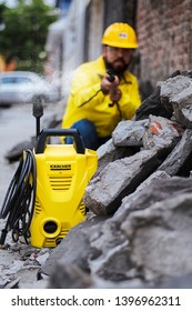 MEXICO CITY, MEXICO - JUNE 27, 2018: Man playing like a soldier with a Karcher machine in the street behind a pail of rocks.