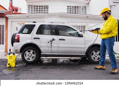 MEXICO CITY, MEXICO - JUNE 27, 2018: Man cleaning the sport van with a waterjet using a Karcher machine.
