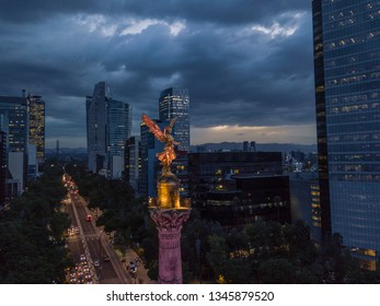 Mexico City - March 17, 2017: frontal aerial view of the statue of the angel of independence on Reforma Avenue with Chapultepec forest and a beautiful sunset in the background