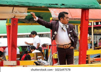 "MEXICO CITY - March 19, 2016: A traditional mariachi band member in classical black uniform, aboard a colorful ""trajinera"" canal gondola boat, play for tourists, on a canal in Xochimilco."