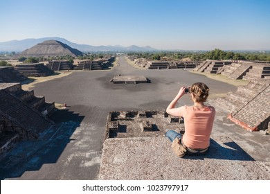 Mexico city, Mexico - march 2nd, 2012: Tourist takes picture of a morning view of an epmty Avenue of The Dead from Pyramid of the Sun in Teotihuacan, Mexico