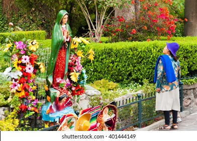 MEXICO CITY - MARCH 30: Indigenous woman stands in front of a statue of the Virgin Mary in Mexico City on March 30, 2013