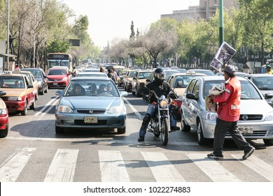 Mexico city, Mexico - MArch 3d, 2012: People sell fresh newspapers early in the morning to a car drivers on a crosswalk on red traffic light in Mexico city, Mexico