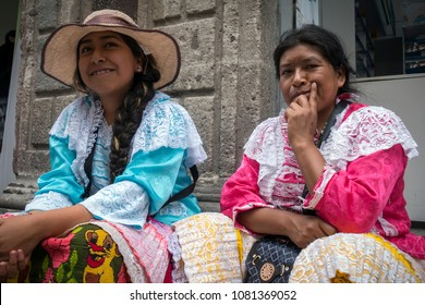 MEXICO CITY, MEX - AUG 14, 2017: Two women in traditional Mexican costume relaxing on the side of a street in the historic part of Mexico City, the capital and most populous city of Mexico
