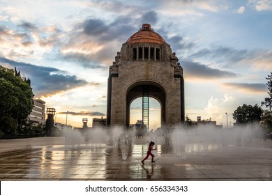 MEXICO CITY, MEXICO - Nov 4, 2016: Girl playing with the water fountain in front of Monument to the Mexican Revolution (Monumento a la Revolucion) - Mexico City, Mexico