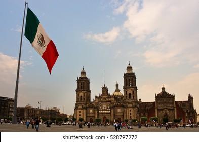 Mexico City, Mexico - November 14, 2016: Big Mexican Flag on Zocalo near Cathedral - Mexico City, Mexico