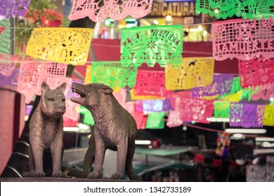 Coyoacán, Mexico City, Mexico - November 19, 2016: Two animal figures made of stone and behind them colorful flags at a famous market place in the center of Coyoacán district.