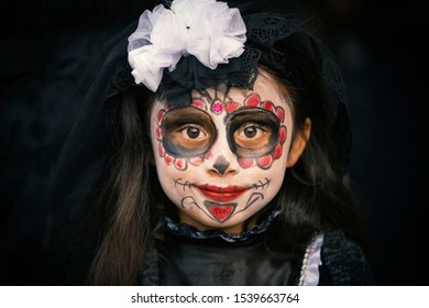 Mexico City, Mexico, November 3, 2018: A Young girl shows off her traditional painted face for Dia De Los Muertos in Mexico.
