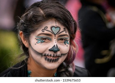 Mexico City / Mexico - November 4, 2018: A young woman with painted face makeup smiles in celebration of Dia De Los Muertos or Day of the Dead, in Mexico.