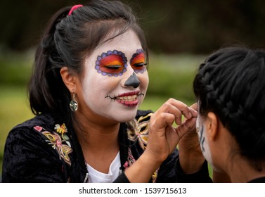 Mexico City / Mexico - November 4, 2018: A smiling woman applies makeup, eyelashes and face paint to a girl for Dia De Los Muertos, or day of the dead in Mexico.