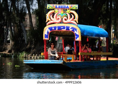 Mexico City, Mexico - Oct 5, 2016. Colorful trajineras or boats full of tourists take a tour on Lake Xochimilco channels. UNESCO World Heritage Site in Mexico City.