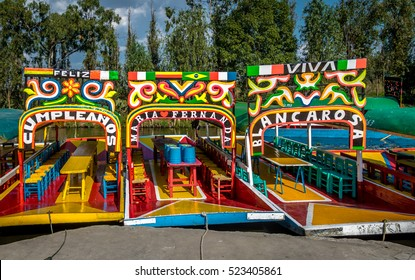 "MEXICO CITY, MEXICO - OCTOBER 13, 2016: Colourful Mexican boats at Xochimilco's Floating Gardens - One boat named ""Happy Birthday"" and the other two with women names - Mexico City, Mexico"