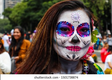Mexico City, Mexico - October 20, 2018: Young Woman with Face Painted in Catrina Skull Make Up for Day of the Dead in Mexico City Parade