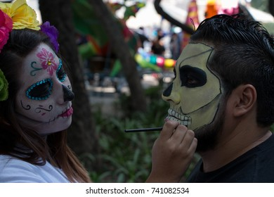 """MEXICO CITY, MEXICO - OCTOBER 22, 2017: makeup artist face painting a man for the """"Catrina"""" parade, female skeletons dressed as upper class Europeans with hats or decorative, colorful flowers"""